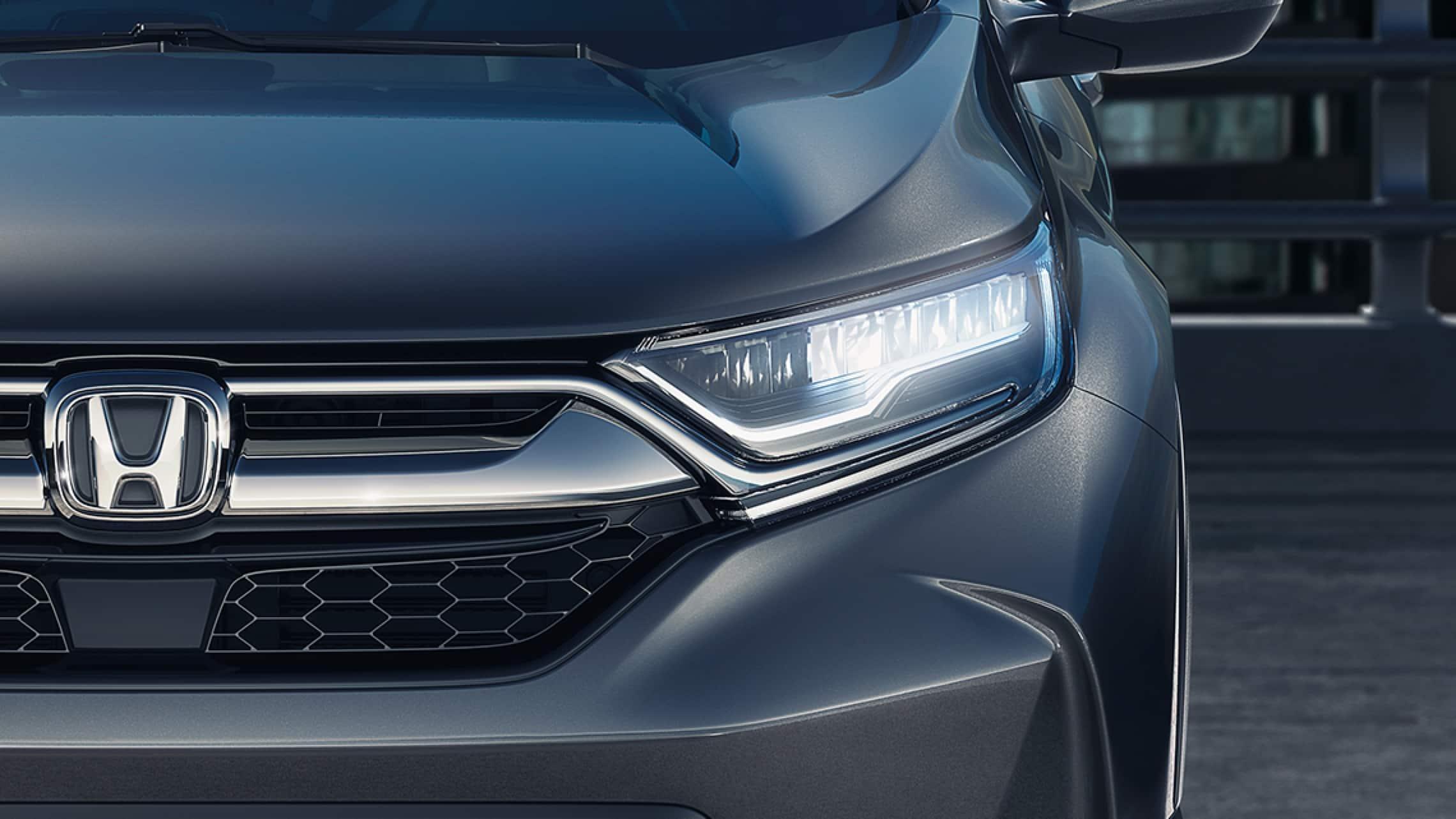 Vista frontal de cerca de la Honda CR-V Touring 2019 con luces delanteras de LED con encendido/apagado automático.