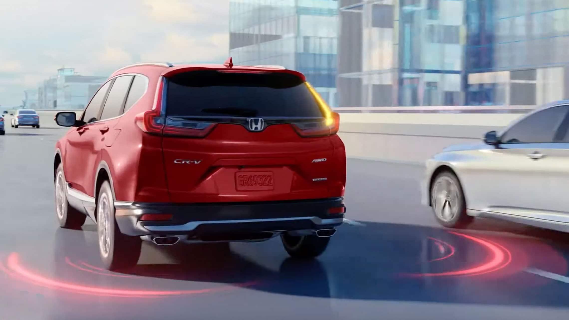 Vista trasera desde el lado del conductor de la Honda CR-V2020 en Radiant Red Metallic, conduciendo por una autopista, con una ilustración que muestra la característica del sistema de información de puntos ciegos.