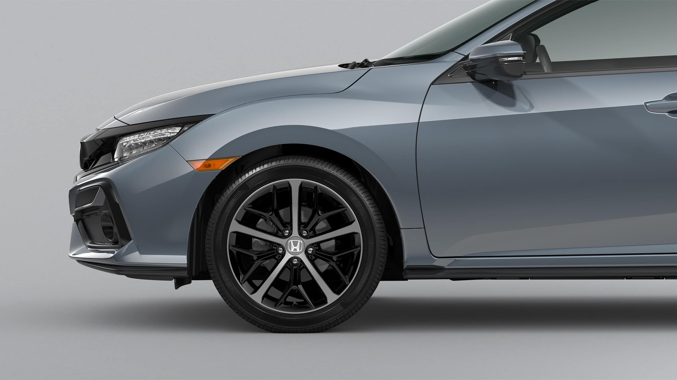 Front passenger-side 18-inch alloy wheel detail on 2020 Honda Civic Sport Touring Hatchback in Sonic Gray Pearl.