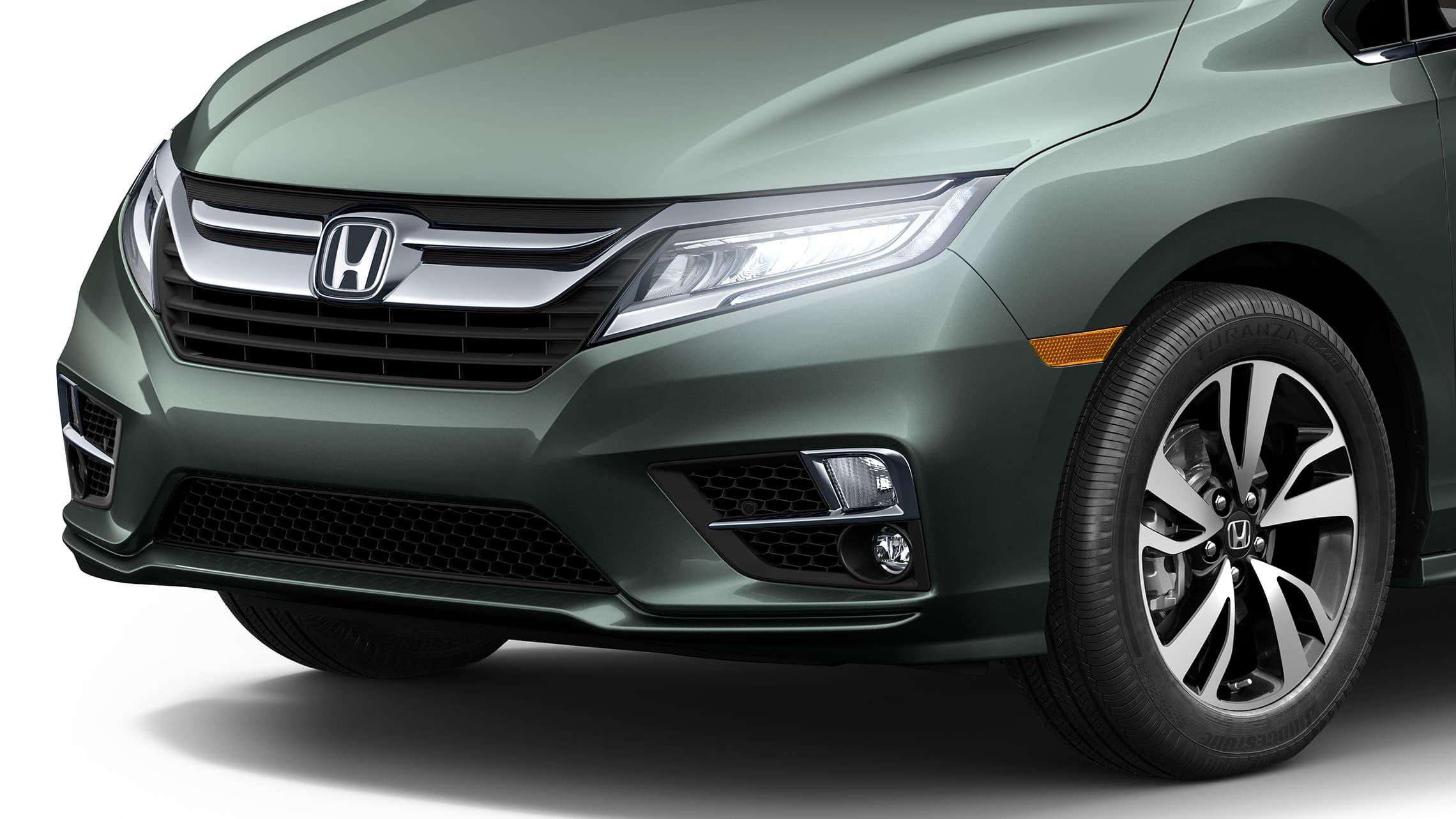 Primer plano frontal de 3/4 desde el lado del conductor de las luces delanteras de la Honda Odyssey Elite2020 en Forest Mist Metallic.