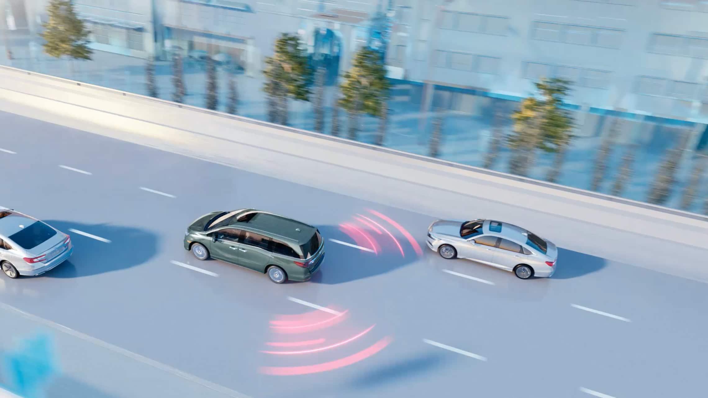 Vista aérea trasera de 3/4 desde el lado del conductor de la Honda Odyssey Elite2020 en Forest Mist Metallic, conduciendo por una autopista, con ilustración de las líneas del sistema de información de puntos ciegos.