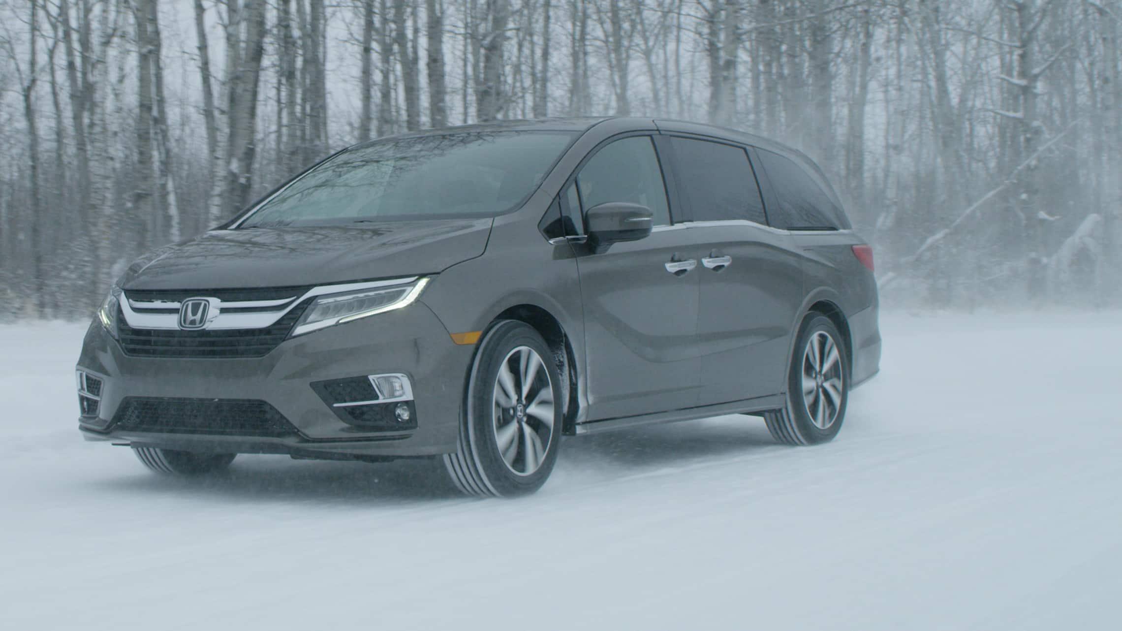 Vista frontal de 3/4 desde el lado del conductor de la Honda Odyssey2020 en Modern Steel Metallic conduciendo por un camino cubierto de nieve.