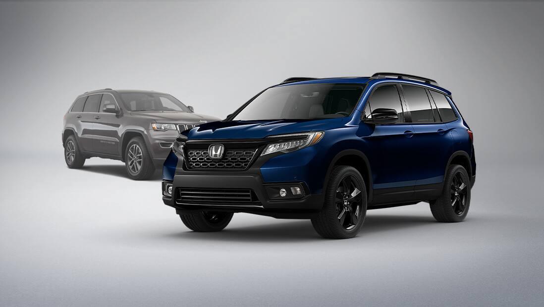 Vista frontal de 3/4 desde el lado del pasajero de la Honda Passport Elite2020 en Obsidian Blue Pearl, estacionada en un estudio junto a una Jeep Grand Cherokee.