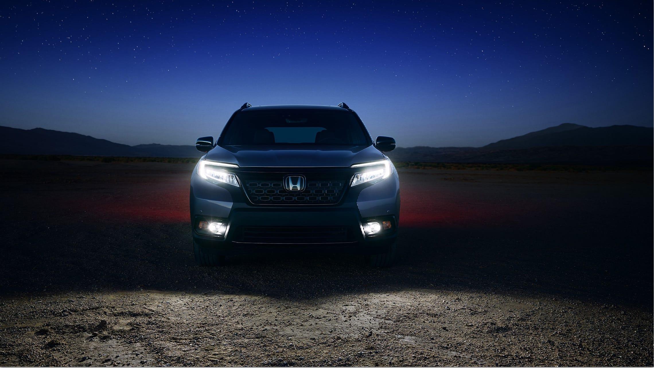 Vista frontal directa de la Honda Passport Elite2020 en Modern Steel Metallic con luces delanteras bajas de LED y faros antiniebla encendidos.