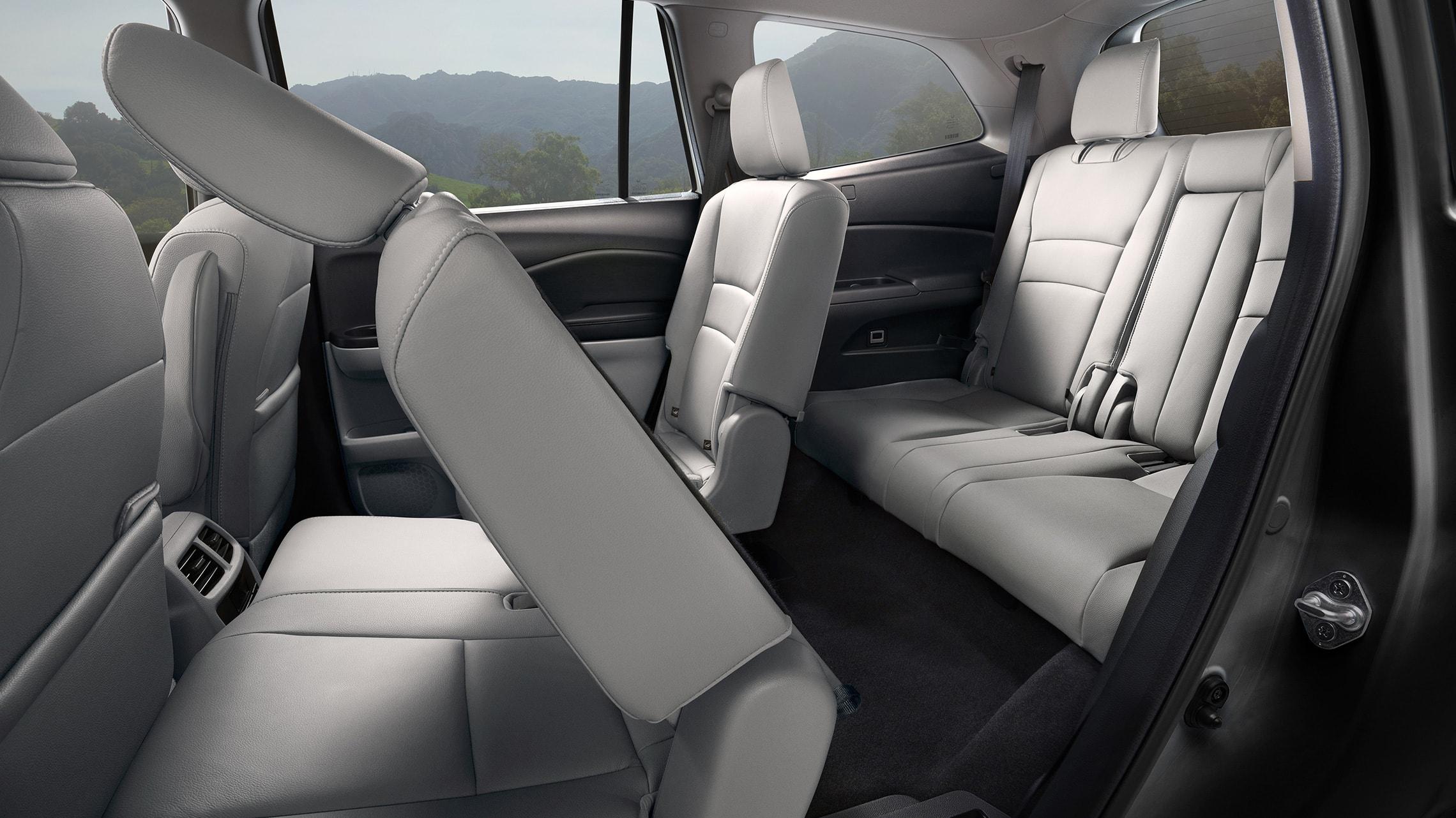 Se muestra el detalle de los asientos tipo capitán en la segunda fila abatidos de la Honda PilotElite2020 con interior en Gray Leather.